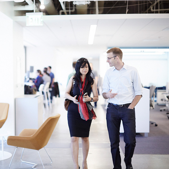 Two people walking together in an office space.