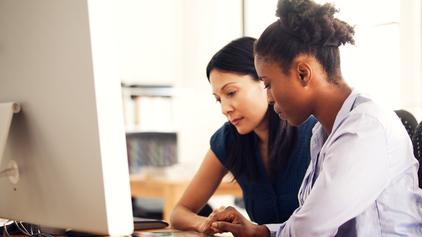 Two women sit in front of a computer and discuss content on screen.
