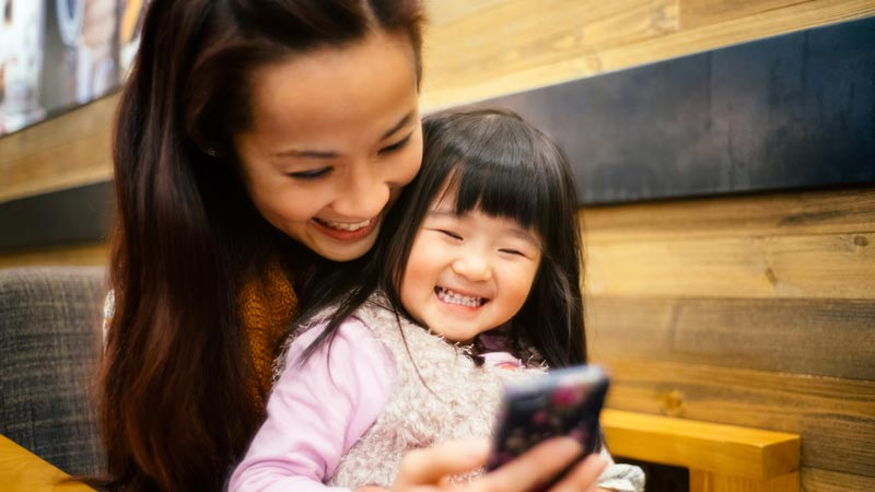 Mum and toddler girl using smartphone joyfully.
