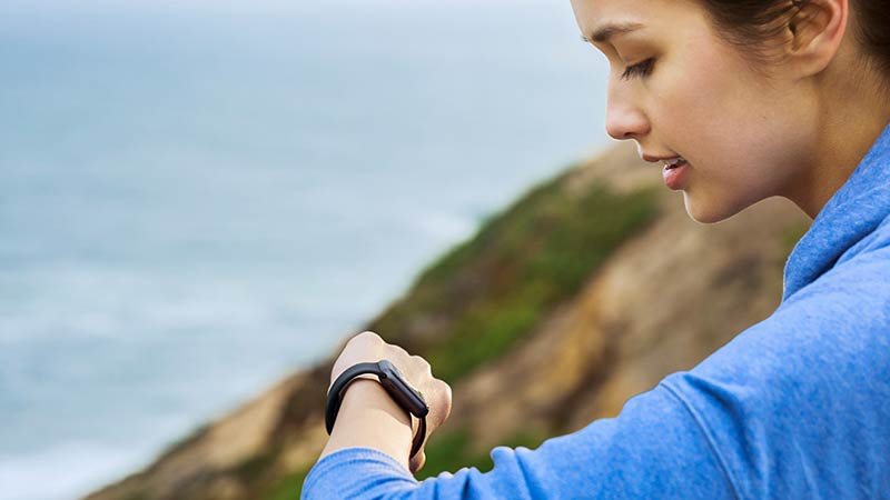 woman looking at smartwatch while hiking